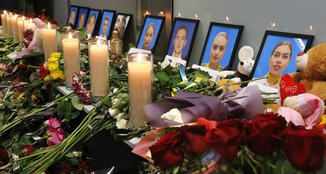 Flowers and candles are placed in front of portraits of the flight crew members of the Ukrainian 737-800 plane that crashed on the outskirts of Tehran, at a memorial inside Borispil International Airport outside Kyiv, Ukraine, Saturday, Jan. 11, 2020. AP Photo