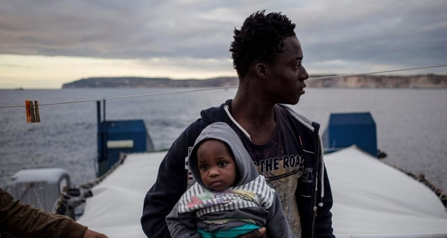 A migrant holds a baby aboard the Dutch-flagged rescue Vessel Sea Watch 3 sailing off Malta's coast (Rear) on January 8, 2019 (AFP Photo)