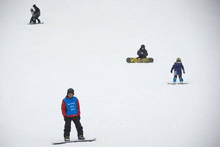 People snowboard at the Wanda Harbin Ice and Snow Park in Harbin.