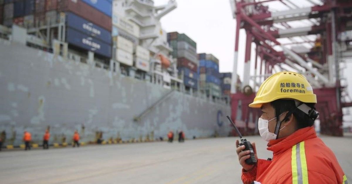 In this Feb. 4, 2020, photo, a foreman wears a face mask as he communicates via radio at a container port in Qingdao in eastern China's Shandong Province. (Chinatopix via AP)