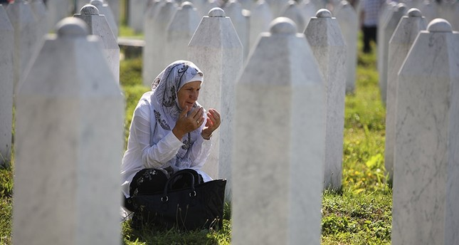 An elderly woman prays between gravestones on the Potocari Memorial Center in Srebrenica, Bosnia and Herzegovina, 11 July 2017. (EPA Photo)