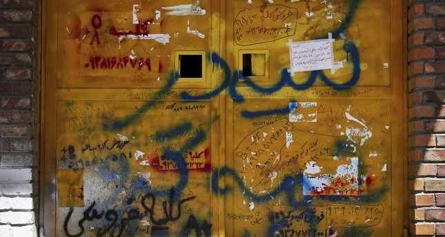 Picture shows handwritten advertisements for kidneys for sale, that include the sellers' phone number and blood type, posted on a door in downtown Tehran.
