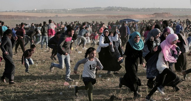 Palestinian protesters run for cover from teargas fired during clashes with Israeli troops along the Gaza Strip, east of Beit Lahiya, March 31.