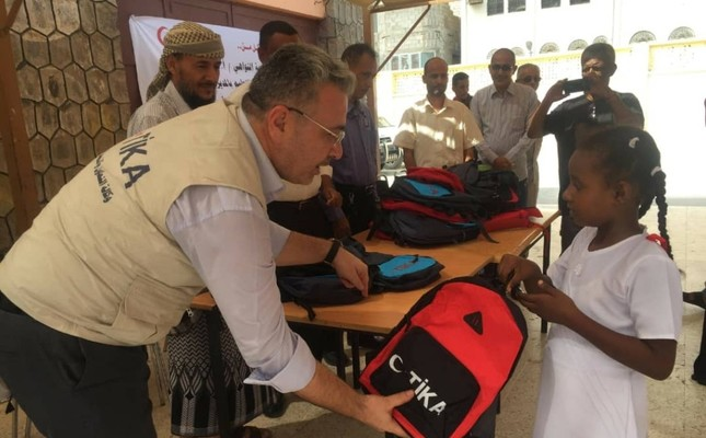 TİKA officials hand out school bags with stationery sets to Yemeni children in Aden in October 2018.