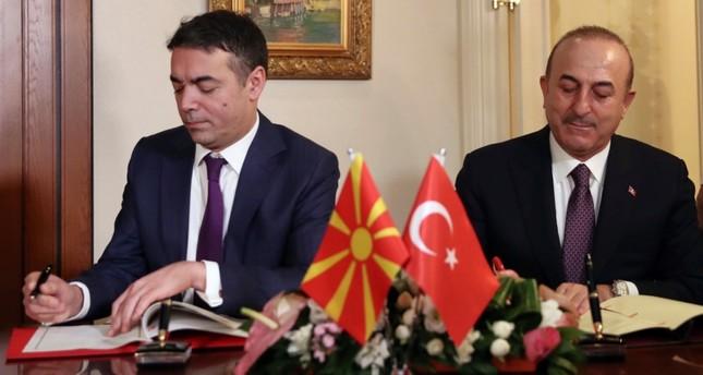 Turkey's Foreign Minister Mevlüt Çavuşoğlu, right, and Macedonia's Foreign Minister Nikola Dimitrov sign an agreement after their talks in Ankara, Turkey, Thursday, Jan. 17, 2019. (Turkish Foreign Ministry via AP, Pool)