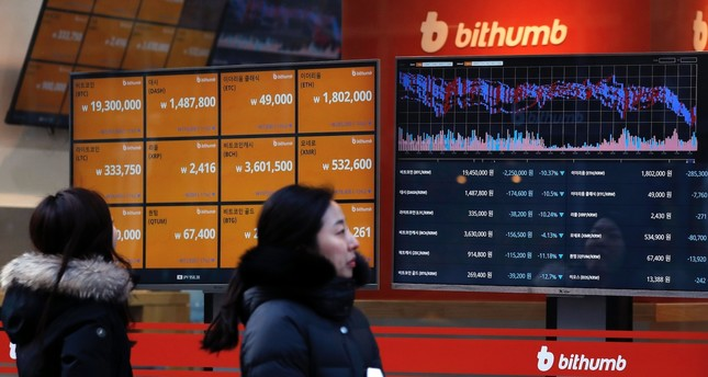 People look at monitors displaying cryptocurrency values at the leading South Korean exchange Bithumb, Seoul, South Korea, Jan. 11.