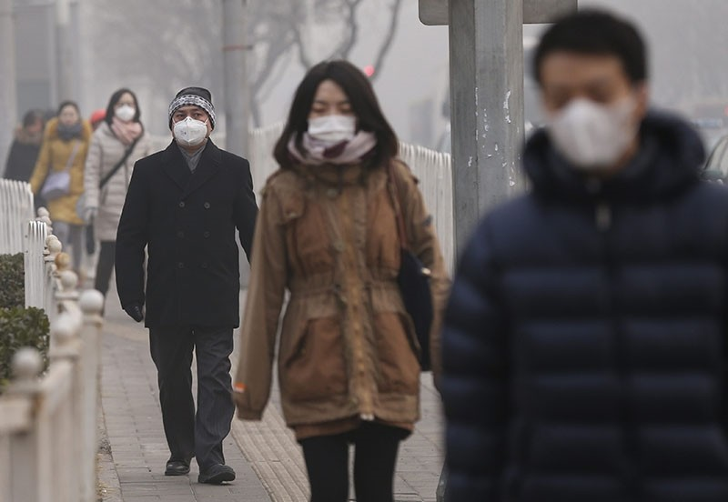 Chinese citizens wear masks on their faces on a hazy day while walking to their respective destinations in Beijing, China, 16 January 2014. (EPA Photo)