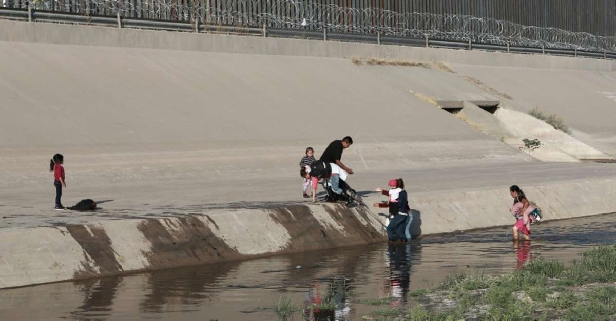 Migrant families cross the rio Grande to get illegally across the border into the United States, to turn themselves in to authorities and ask for asylum, next to the Paso del Norte international bridge, near El Paso, Texas. (AP Photo)