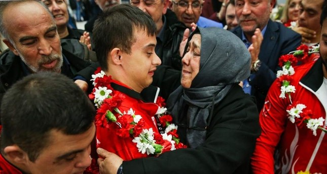 Semiha Erdem hugs her son Talha Ahmet Erdem at the airport as he returns from Portugal after winning gold, Dec. 2, 2019. AA Photo