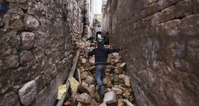 A Syrian boy makeing his way through the rubble of destroyed buildings as he heads to his house in Aleppo's Dahret Awad neighbourhood on Dec. 17, 2016.