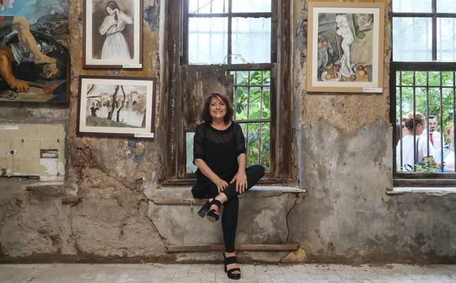 Artist Heyecan Şahin posing with her works.