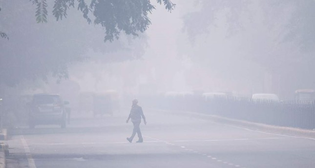 A man crosses a street in smoggy conditions in New Delhi, Nov. 4, 2019. (AFP Photo)