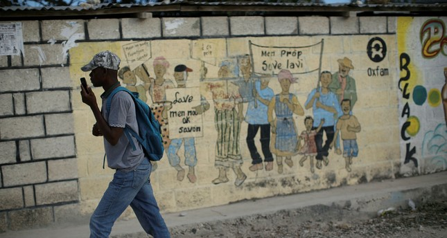 A man walks past an Oxfam sign in Corail, a camp for displaced people of the 2010 earthquake, Haiti, Feb. 13.