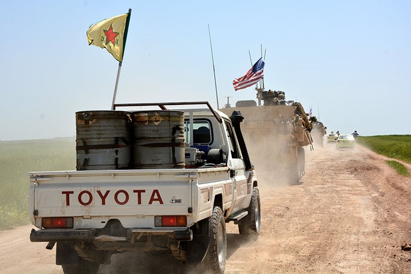A convoy of US army troops and militants from PKK's Syrian offshoot the People's Protection Units (YPG) patrol near al-Ghanamya village, al-Darbasiyah town at the Syrian-Turkish border, Syria, April 29, 2017. (EPA Photo)