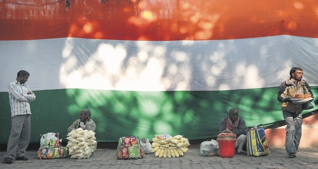 Indian vendors wait for customers near an Indian national flag, New Delhi, India, Dec. 28.