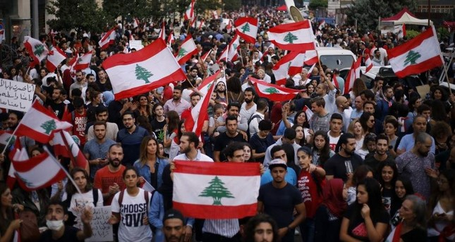 Demonstrators chant slogans against the Lebanese government as they hold Lebanese national flags during a protest in Beirut, Lebanon, Oct. 26, 2019. AP