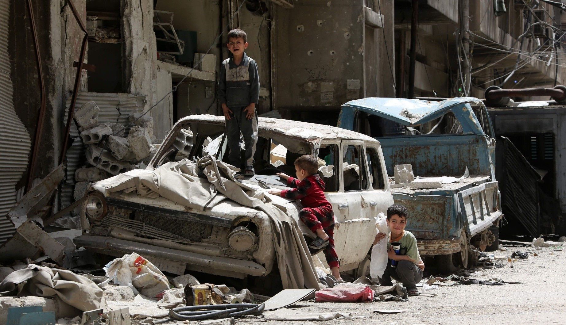Syrian boys play on a destroyed car, Douma, on the outskirts of Damascus, April 19.