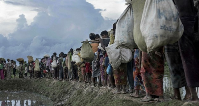 Rohingya refugees walk after crossing the Naf river from Myanmar into Bangladesh in Whaikhyang.