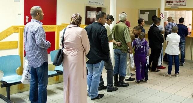 لاجئون سوريون يقفون أمام مكتب التسجيل بُعيد وصولهم من الأرشيف
