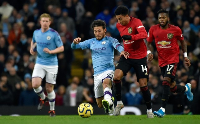 Manchester City's David Silva, center left, duels for the ball with Manchester United's Jesse Lindgard during the Premier League soccer match between Manchester City and Manchester United at Etihad stadium in Manchester, Dec. 7, 2019. AP Photo