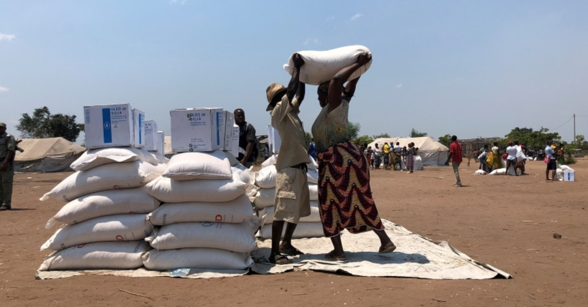 A man helps a woman lift a bag of aid during a distribution for victims of Cyclone Idai at a camp in Guara Guara, outside Beira, Mozambique, October 8, 2019, Picture taken October 8, 2019. (Reuters Photo)