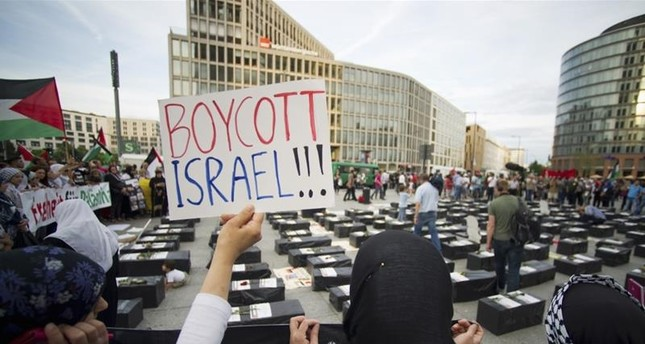 A woman holds a sign which reads Boycott Israel in front of symbolic coffins while attending a demonstration supporting Palestine, in Berlin August 1, 2014. (REUTERS Photo)