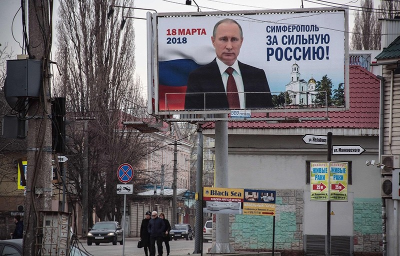 People walk past campaign billboards of Russian President Vladimir Putin, reading ,Simferopol for the Strong Russia!, in Simferopol, Ukraine. (AFP Photo)