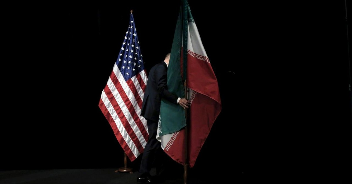A staff member removes the Iranian flag from the stage after a group picture with foreign ministers and representatives during Iran nuclear talks at the Vienna International Center in Vienna, Austria, July 14, 2015. (Reuters Photo)