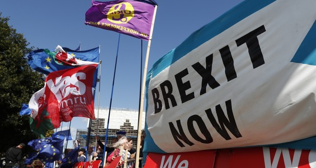 Remain and leave supporters wave flags and hold banners during a demonstration outside the gates of Parliament in London, Sept. 4, 2019.