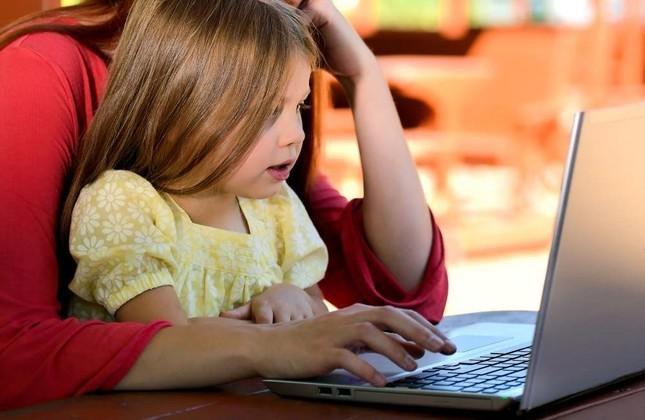 A small girl plays with a computer under the supervision of an adult. (File photo)