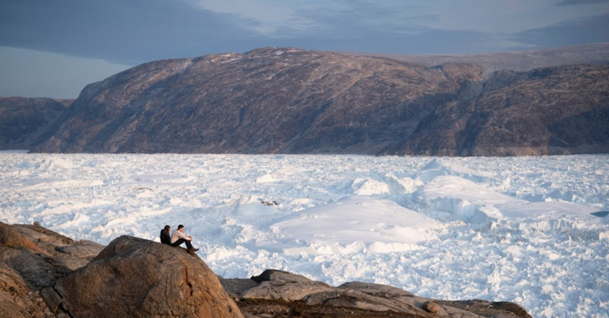 In this Aug. 16, 2019, photo, New York University student researchers sit on a rock overlooking the Helheim glacier in Greenland. (AP Photo)