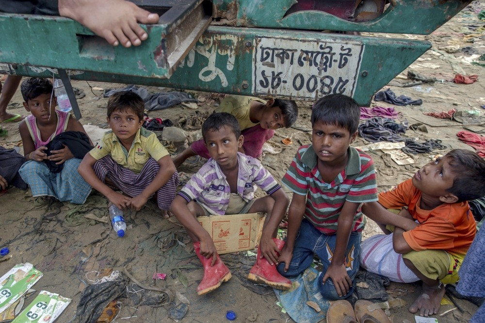 Rohingya Muslim children, who crossed over from Myanmar into Bangladesh, sit under a truck carrying relief material and watch food being distributed near Taiy Khali refugee camp.