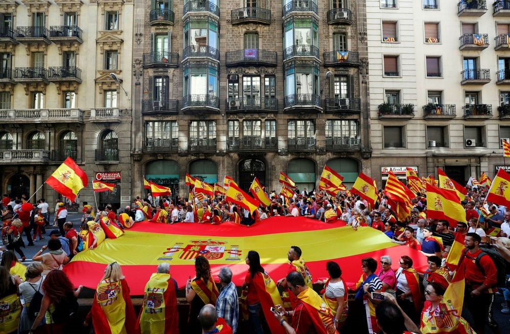 Protestors carry a giant Spanish flag during a rally in favor of the unity of Spain in Barcelona, Spain, Oct. 8.