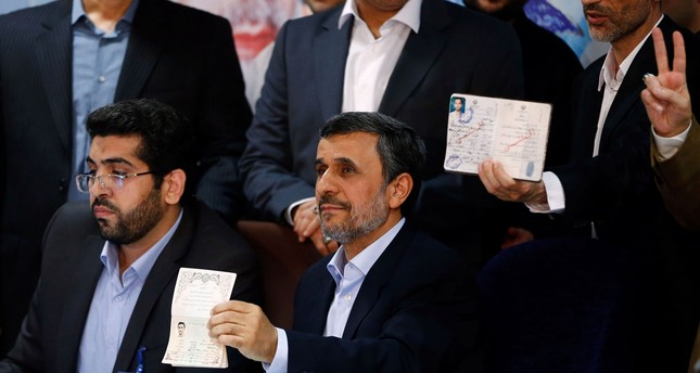 Former Iranian president Mahmoud Ahmadinejad (C) displays identification at the Interior Ministry's election headquarters as candidates begin to sign up for the upcoming presidential elections in Tehran on April 12, 2017. (AFP Photo)