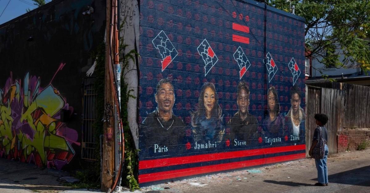 A girl looks at a mural depicting teenage gun violence victims, Washington, D.C., Sept. 11, 2019.