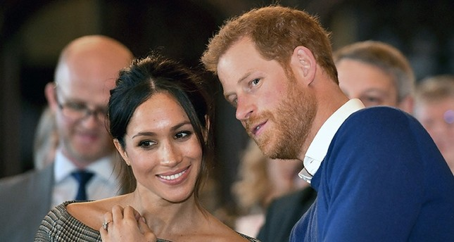 In this Thursday Jan. 18, 2018 file photo, Britain's Prince Harry talks to Meghan Markle as they watch a dance performance by Jukebox Collective in the banqueting hall during a visit to Cardiff Castle, Wales. AP Photo