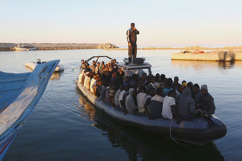 frican migrants are seen seated in a boat, after being rescued by the Libyan navy following their boat suffering engine failure, near the coastal town of Gharaboli (Reuters Photo)