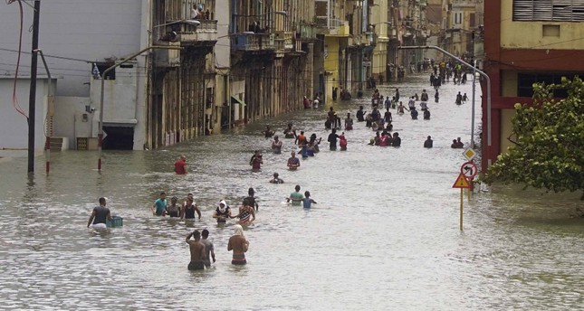People move through flooded streets in Havana after the passage of Hurricane Irma, in Cuba.