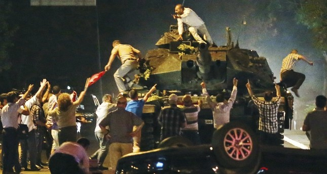 A tank moving into position as Turkish people clamber onto it, attempting to stop the Gülenist military coup, in Ankara, July 16.