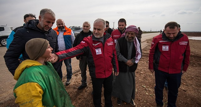 Turkish Red Crescent Chairman Kerem Kınık (center) talks with migrants in the Azez region of Afrin. (AA Photo)