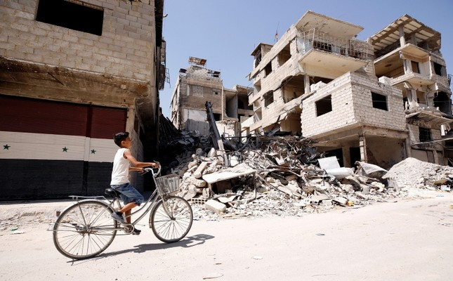 A boy rides on a bicycle along a damaged street in the town of Kafr Batna, in eastern Ghouta, Syria, Sept. 5, 2018. (Reuters Photo)