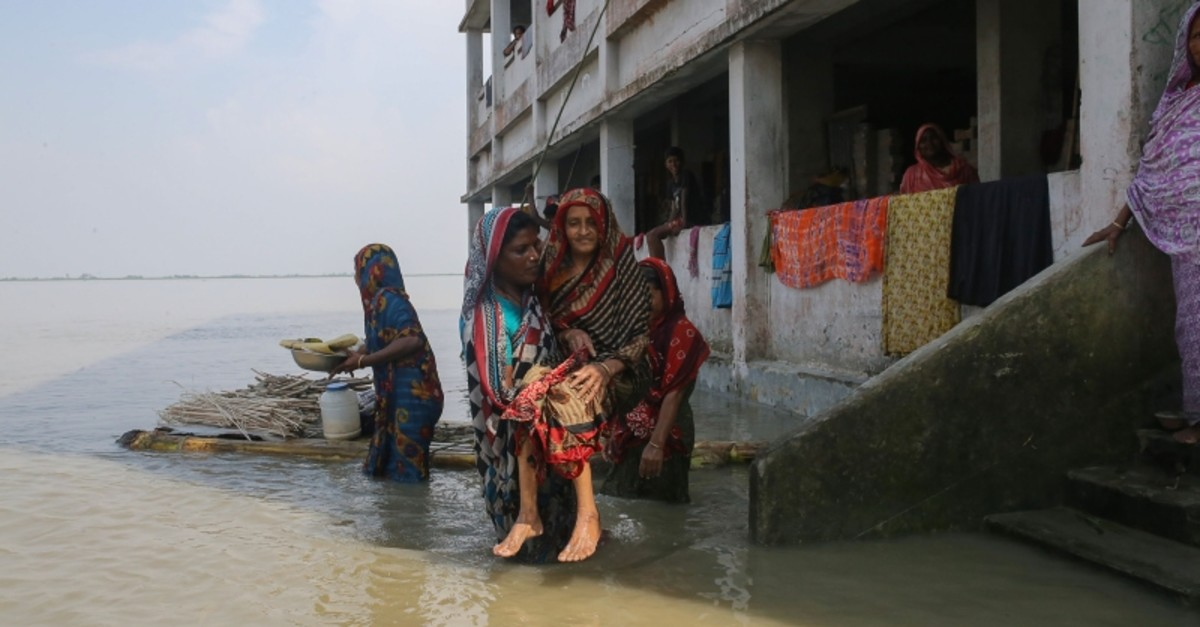 A woman holds an elderly following heavy monsoon rains at a flood affected area of Gaibandha District, in Northern Bangladesh, on July 19, 2019. (AFP Photo)
