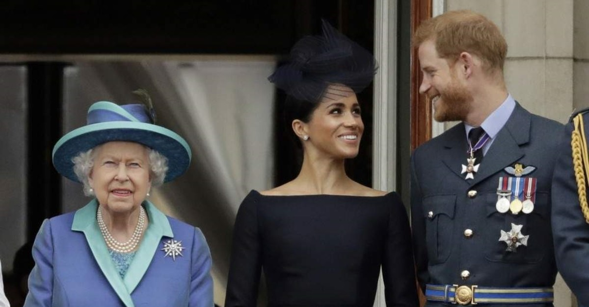 Britain's Queen Elizabeth II, Meghan the Duchess of Sussex and Prince Harry watch a flypast of Royal Air Force aircraft over Buckingham Palace, London, July 10, 2018. (AP Photo)