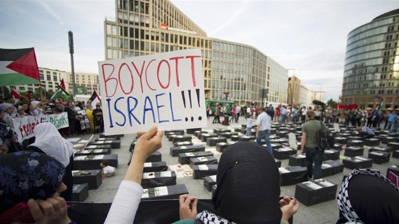 A woman holds a sign which reads ,Boycott Israel, in front of symbolic coffins while attending a demonstration supporting Palestine, in Berlin August 1, 2014. (REUTERS Photo)