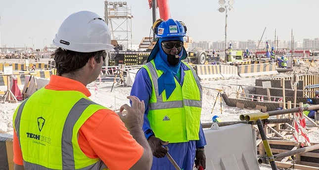 A handout picture released by Qatar World Cup organizers on Sept. 1, 2018, shows two employees at Losail Studium in the Qatari capital of Doha. (AFP Photo)