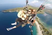 Multitasking at its best: Chinese artist Xu Fei plays guitar while paragliding in Fethiye
