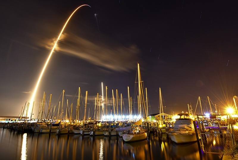 In this image made with an 8-minute long exposure the SpaceX Falcon 9 rocket launches from Cape Canaveral Air Force Station and lands as seen from from the Ocean Club Marina in Port Canaveral, Fla., Jan. 7, 2018. (AP Photo)