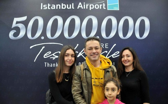 The Kobanbay family poses in front of a sign marking the 50 millionth passenger at the airport. DHA Photo