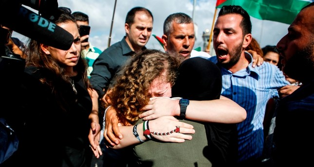 Palestinian activist and campaigner Ahed Tamimi (C) embraces her mother upon her release from prison after an eight-month sentence for slapping two Israeli soldiers, in the West Bank village of Nabi Saleh on July 29, 2018. (AFP Photo)