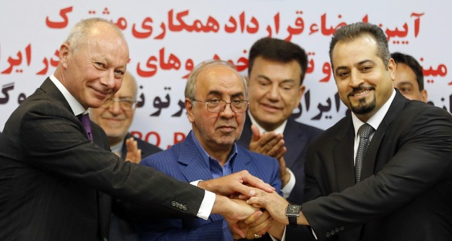 (L to R) Bollore, deputy director of competitiveness at Renault, Moazami, chairman of the board of directors of the IDRO Group, and  Solouk, deputy director of the Iranian Automobile Importers Association, shake hands in Tehran Monday.
